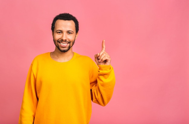 Porträt eines lächelnden glücklichen mannes im lässigen zeigen mit den fingern beiseite lokalisiert über rosa.