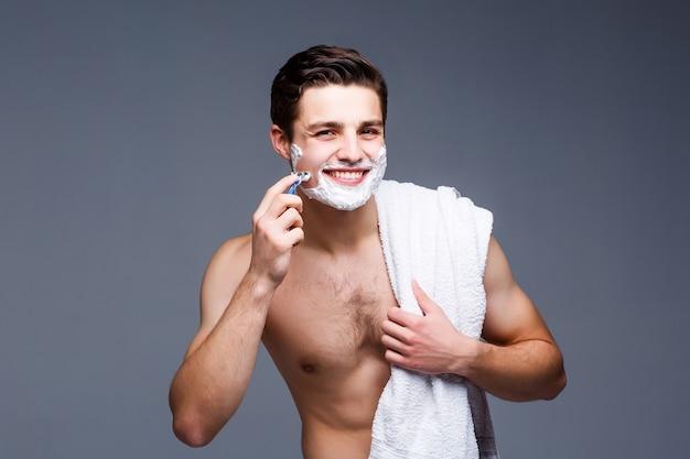 Porträt eines lächelnden, gutaussehenden rasierenden mannes in der morgenzeit, isoliert auf grauer wand