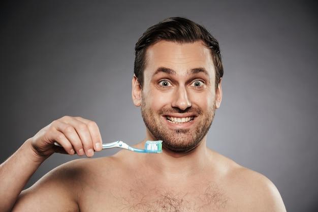 Porträt eines lächelnden hemdlosen mannes, der zahnbürste hält