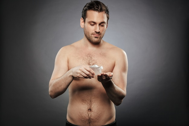 Porträt eines lächelnden hemdlosen mannes unter verwendung der aftershave-lotion