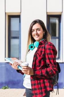 Porträt eines lächelnden hochschulstudenten, der in der hand bücher und die wegwerfkaffeetasse zur kamera schaut hält