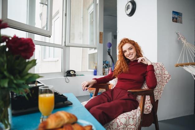 Porträt eines lächelnden hübschen mädchens, das auf einem stuhl sitzt