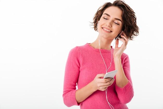 Porträt eines lächelnden hübschen mädchens, das musik hört