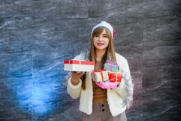 Porträt eines lächelnden hübschen mädchens, das stapel geschenkboxen über grauem hintergrund hält