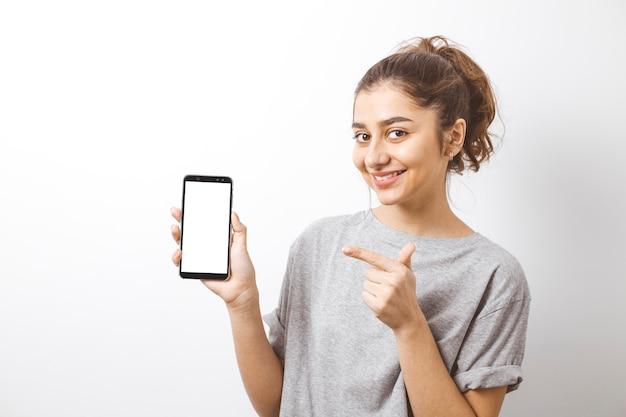 Porträt eines lächelnden indischen mädchens, das finger auf dem weißen schirm des smartphone zeigt.