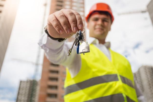 Porträt eines lächelnden ingenieurs, der schlüssel aus dem neuen zuhause zeigt