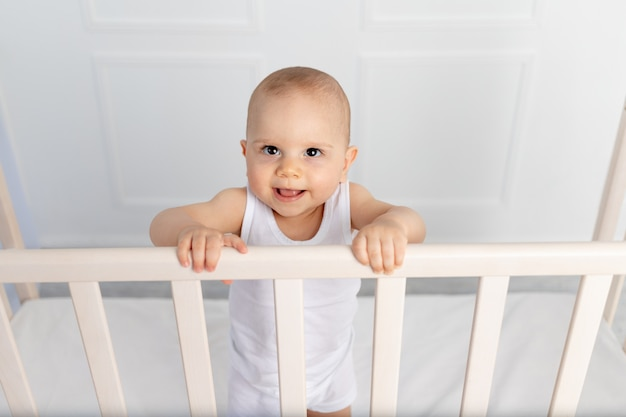 Porträt eines lächelnden jungen 8 monate alt stehend in einem kinderbett in einem kinderzimmer in weißen kleidern und l, morgenbaby, babyproduktkonzept