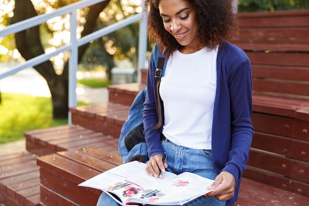 Porträt eines lächelnden jungen afrikanischen mädchens mit dem rucksack, der am park, das magazin liest, ruht