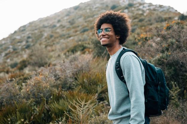 Porträt eines lächelnden jungen afrikanischen mannes mit seinem rucksack