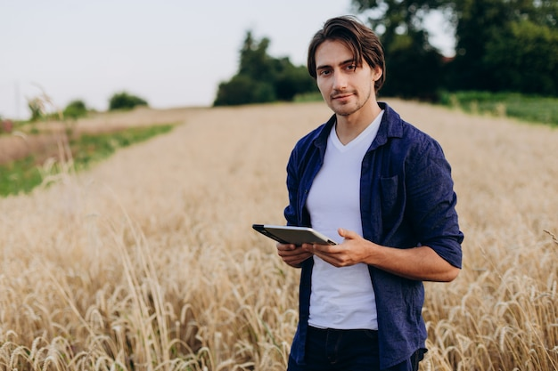 Porträt eines lächelnden jungen agronomen, der auf einem weizengebiet mit ipad steht