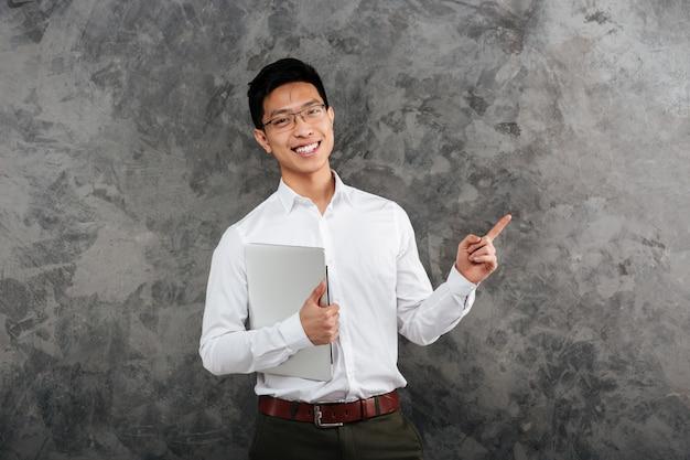 Porträt eines lächelnden jungen asiatischen mannes gekleidet im hemd