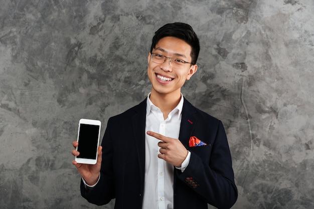 Porträt eines lächelnden jungen asiatischen mannes im anzug gekleidet