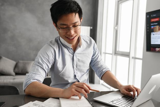 Porträt eines lächelnden jungen asiatischen mannes unter verwendung des laptops