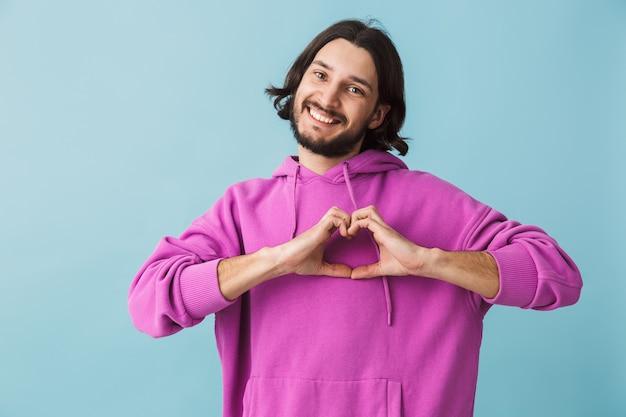 Porträt eines lächelnden jungen bärtigen brünetten mannes mit hoodie, der isoliert über blauer wand steht und liebesgeste zeigt