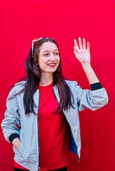 Porträt eines lächelnden jungen brünetten mädchens, das einer anderen person auf flachem rotem hintergrund zuwinkt