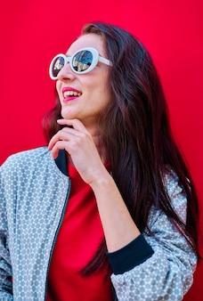 Porträt eines lächelnden jungen brunettemädchens mit sonnenbrille auf flachem rotem hintergrund red