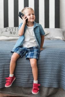 Porträt eines lächelnden jungen, der auf dem bett spricht am intelligenten telefon sitzt