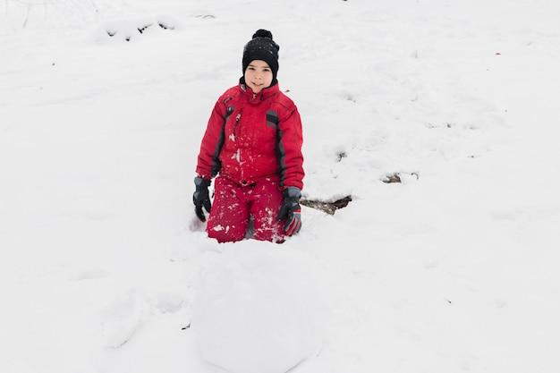 Porträt eines lächelnden jungen, der auf dem schneebedeckten land betrachtet kamera sitzt