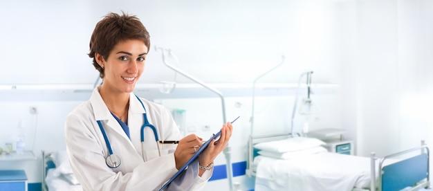 Porträt eines lächelnden jungen doktorschreibens auf einem klemmbrett
