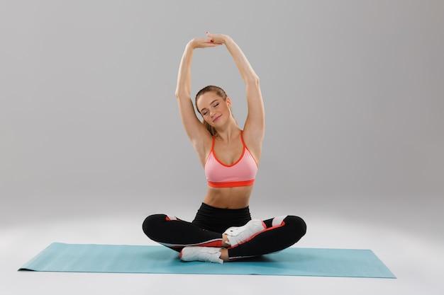 Porträt eines lächelnden jungen fitnessmädchens, das hand streckt