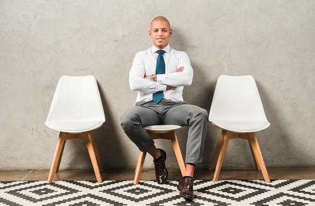 Porträt eines lächelnden jungen geschäftsmannes, der auf stuhl mit seinem arm gekreuzt sitzt