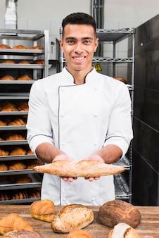Porträt eines lächelnden jungen männlichen bäckers, der stangenbrotbrot hält