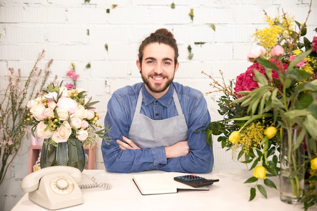 Porträt eines lächelnden jungen männlichen floristen mit den bunten blumen im shop