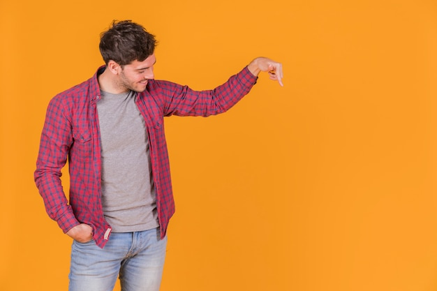 Porträt eines lächelnden jungen mannes, der abwärts seinen finger auf einem orange hintergrund zeigt