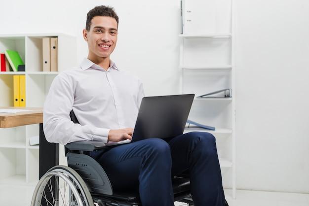 Porträt eines lächelnden jungen mannes, der auf rollstuhl mit dem laptop betrachtet kamera sitzt