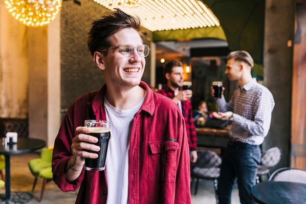Porträt eines lächelnden jungen mannes, der das bierglasgenießen hält