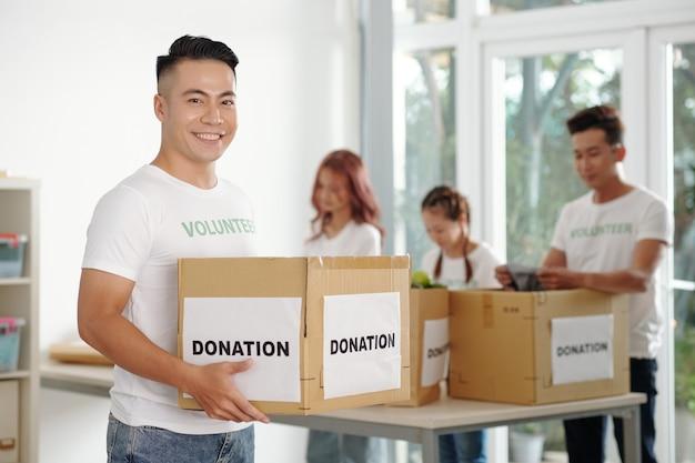 Porträt eines lächelnden jungen mannes, der eine spendenbox hält, seine mitarbeiter, die kleidung und lebensmittel im hintergrund sortieren