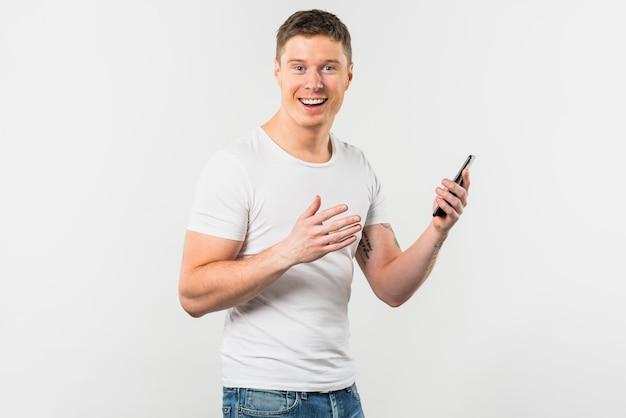 Porträt eines lächelnden jungen mannes, der in der hand den handy schaut zur kamera hält