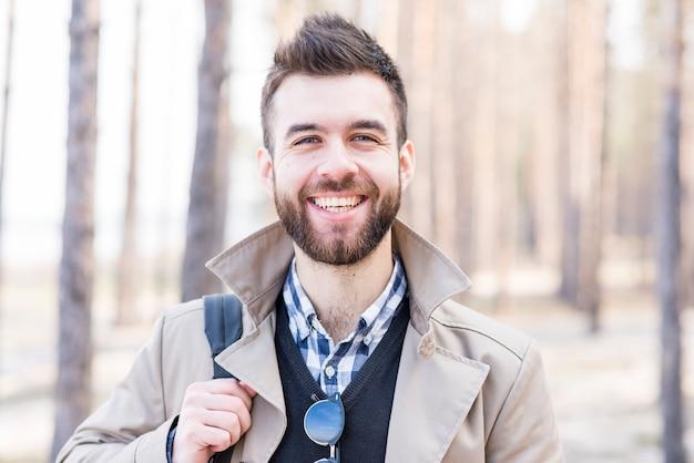 Porträt eines lächelnden jungen mannes, der kamera betrachtet