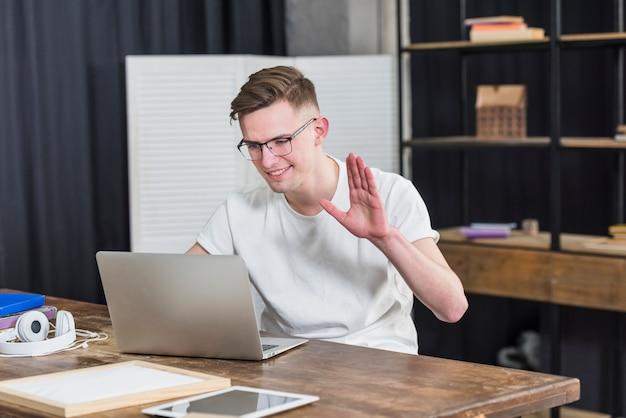Porträt eines lächelnden jungen mannes, der seine hand beim plaudern am video auf laptop wellenartig bewegt