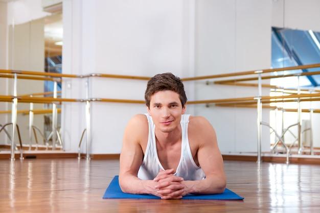 Porträt eines lächelnden jungen mannes, der sit-ups im fitnessstudio macht, blaue matte