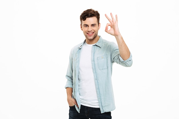 Porträt eines lächelnden jungen mannes, der steht und ok zeigt