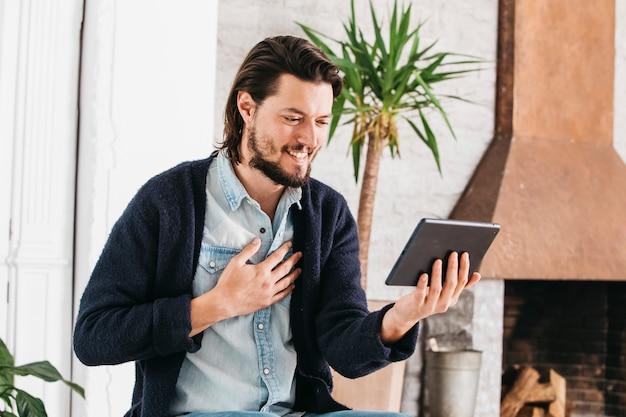 Porträt eines lächelnden jungen mannes, der videoanruf unter verwendung der digitalen tablette macht