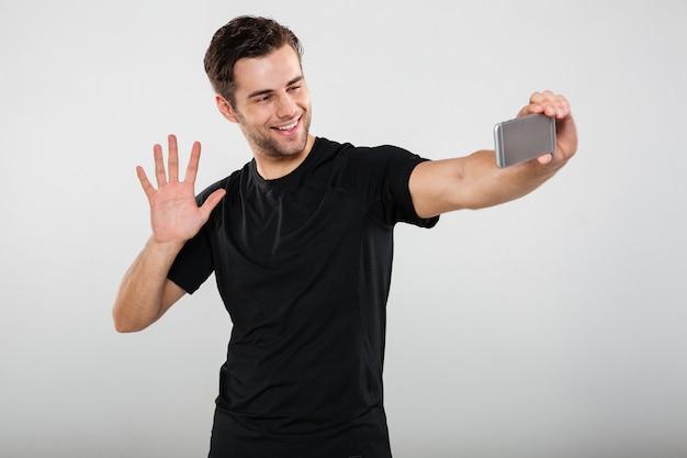 Porträt eines lächelnden jungen mannes, der zur kamera winkt