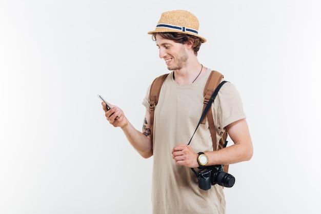 Porträt eines lächelnden jungen mannes mit rucksack und kamera unter verwendung des smartphones lokalisiert auf einem weißen hintergrund