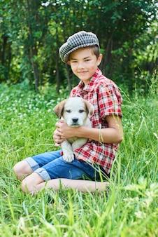 Porträt eines lächelnden jungen mit einem welpen in ihren armen, die auf gras sitzen