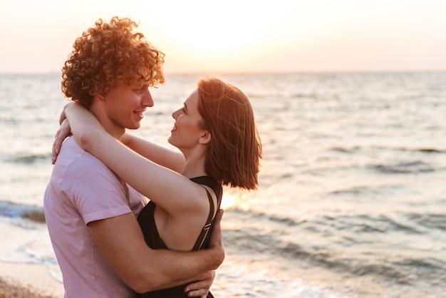 Porträt eines lächelnden jungen paares, das am strand umarmt