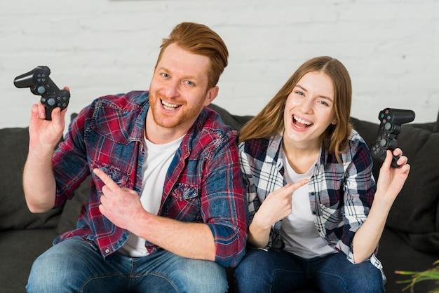 Porträt eines lächelnden jungen paares, das finger in richtung zum videospielprüfer zeigt