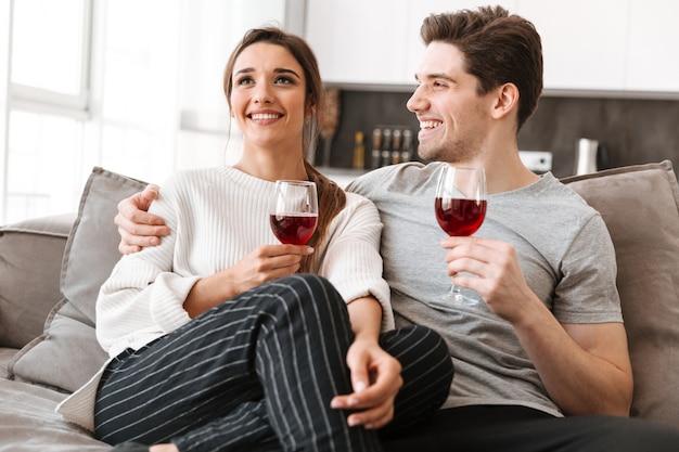 Porträt eines lächelnden jungen paares, das sich auf einer couch entspannt
