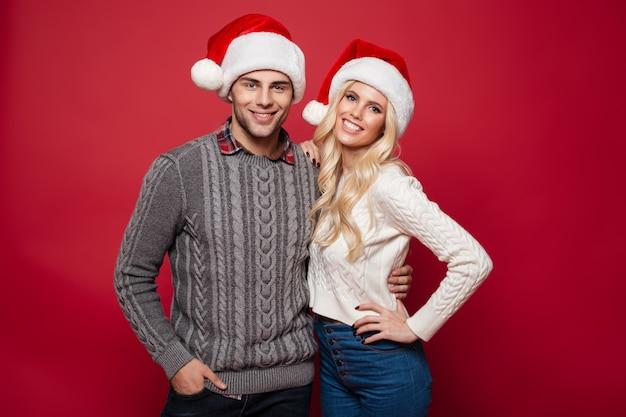 Porträt eines lächelnden jungen paares in den weihnachtsmützen, die umarmen
