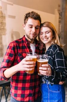 Porträt eines lächelnden jungen paares, welches die gläser des bieres zujubelt