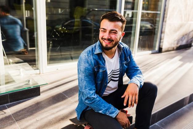Porträt eines lächelnden jungen skateboardfahrers, der auf treppenhaus sitzt