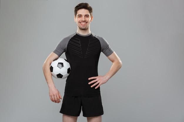 Porträt eines lächelnden jungen sportlers mit einem fußball