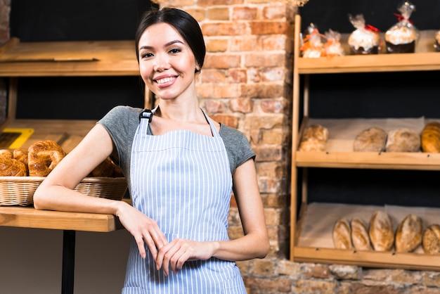 Porträt eines lächelnden jungen weiblichen bäckers, der kamera betrachtet