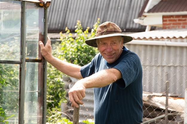 Porträt eines lächelnden kaukasischen älteren männlichen gärtners im hut und im blauen t-shirt.
