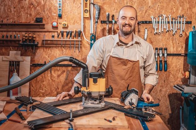 Porträt eines lächelnden kaukasischen zimmermanns mit schürze in seiner werkstatt